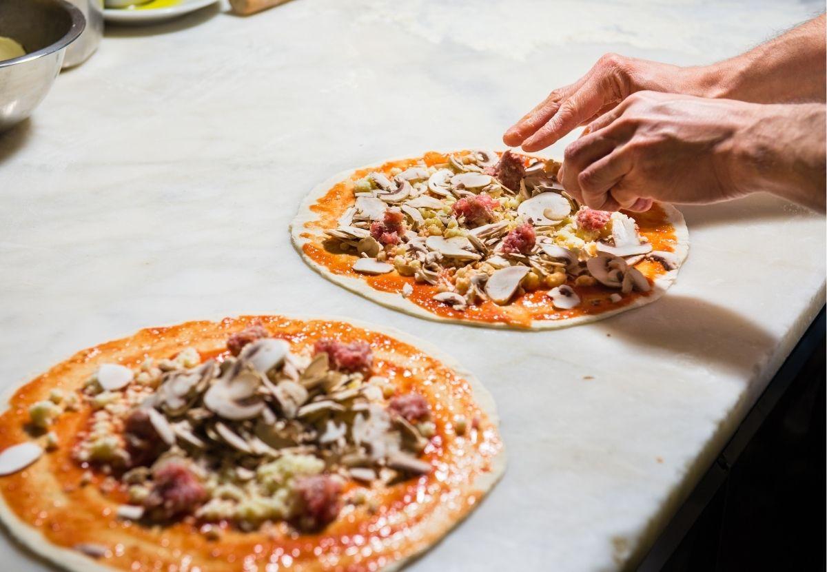 mani che finiscono di condire una pizza stesa sul marmo da lavoro del pizzaiolo