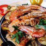 grigliata mista di pesce servita con frutta e verdura grigliate